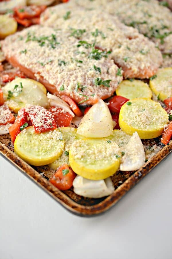 paremesan crusted salmon over sliced vegetables on a baking sheet