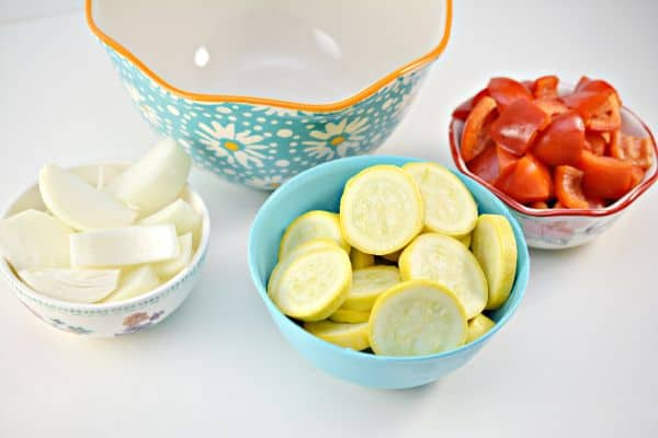 bowl of sliced onions, bowl of sliced yellow squash, bowl of sliced red bell pepper arranged around larger empty bowl